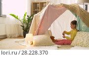 Купить «happy girl in kids tent playing tea party at home», видеоролик № 28228370, снято 23 февраля 2018 г. (c) Syda Productions / Фотобанк Лори