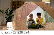 Купить «happy boys reading book in kids tent at home», видеоролик № 28228394, снято 23 февраля 2018 г. (c) Syda Productions / Фотобанк Лори