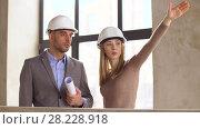 Купить «architects with blueprint and helmets at office», видеоролик № 28228918, снято 4 марта 2018 г. (c) Syda Productions / Фотобанк Лори