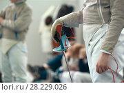 Купить «Young fencer holding rapier in his hand on the fencing tournament», фото № 28229026, снято 26 марта 2018 г. (c) Константин Шишкин / Фотобанк Лори
