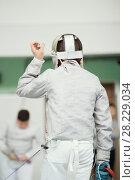 Купить «Back of young fencer in white costume and protective mask», фото № 28229034, снято 26 марта 2018 г. (c) Константин Шишкин / Фотобанк Лори