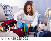 Girl starting packing luggage for journey at home. Стоковое фото, фотограф Яков Филимонов / Фотобанк Лори