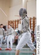 Купить «Young fencer at the fencing competition with sword and mask», фото № 28229886, снято 26 марта 2018 г. (c) Константин Шишкин / Фотобанк Лори