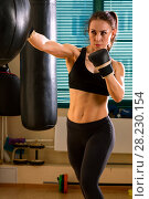 Купить «Strong woman in time of workout at boxer club», фото № 28230154, снято 21 марта 2018 г. (c) Владимир Мельников / Фотобанк Лори