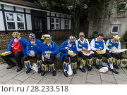 Купить «A Group Of Morris Men Sit On A Wall Eating Fish and Chips During The Annual Lewes Folk Festival, Lewes, Sussex, UK.», фото № 28233518, снято 14 октября 2017 г. (c) age Fotostock / Фотобанк Лори