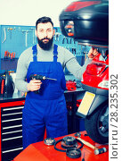Купить «smiling man worker ready to repair motorcycle in workshop», фото № 28235302, снято 22 сентября 2018 г. (c) Яков Филимонов / Фотобанк Лори