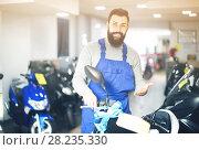 Купить «friendly man worker displaying various motorcycles in workshop», фото № 28235330, снято 21 сентября 2019 г. (c) Яков Филимонов / Фотобанк Лори