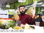 Купить «man seller showing pineapples», фото № 28235462, снято 15 ноября 2016 г. (c) Яков Филимонов / Фотобанк Лори