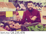 Купить «Male seller offering onions», фото № 28235478, снято 15 ноября 2016 г. (c) Яков Филимонов / Фотобанк Лори