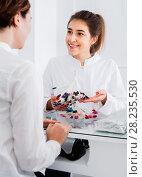 Купить «Female manicurist showing lacquer color schemes», фото № 28235530, снято 2 февраля 2017 г. (c) Яков Филимонов / Фотобанк Лори