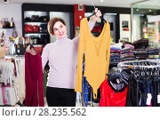 Купить «Ordinary female deciding on pretty blouse», фото № 28235562, снято 7 февраля 2017 г. (c) Яков Филимонов / Фотобанк Лори