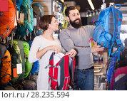 Купить «friendly couple examining rucksacks in sports equipment store», фото № 28235594, снято 24 февраля 2017 г. (c) Яков Филимонов / Фотобанк Лори