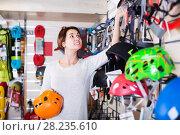 Купить «Woman choosing helmet in store», фото № 28235610, снято 24 февраля 2017 г. (c) Яков Филимонов / Фотобанк Лори