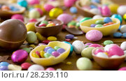 Купить «chocolate easter eggs and drop candies on table», видеоролик № 28239110, снято 24 марта 2018 г. (c) Syda Productions / Фотобанк Лори