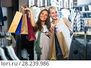 Купить «two girls with shopping bags in shop», фото № 28239986, снято 14 декабря 2019 г. (c) Яков Филимонов / Фотобанк Лори