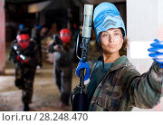 Купить «woman in blue mask is making selfie on battlefield of paintball club.», фото № 28248470, снято 10 июля 2017 г. (c) Яков Филимонов / Фотобанк Лори