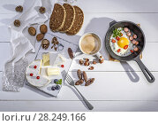 Купить «Camembert cheese, a cup of coffee and a black cast-iron frying pan with a fried egg on a white wooden table, top view.», фото № 28249166, снято 21 февраля 2018 г. (c) age Fotostock / Фотобанк Лори