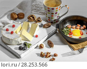 Купить «Coffee, fried eggs in a white black cast-iron frying pan and camembert cheese on a white wooden board.», фото № 28253566, снято 21 февраля 2018 г. (c) age Fotostock / Фотобанк Лори