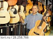 Купить «Mature man choosing acoustic guitar», фото № 28258766, снято 18 сентября 2017 г. (c) Яков Филимонов / Фотобанк Лори