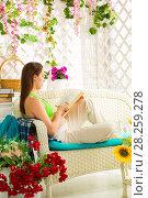 Купить «Young pregnant woman reading a book in a summer terrace», фото № 28259278, снято 3 апреля 2018 г. (c) Владимир Мельников / Фотобанк Лори