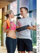 Купить «smiling young woman with personal trainer in gym», фото № 28260970, снято 29 июня 2014 г. (c) Syda Productions / Фотобанк Лори