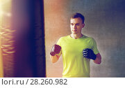 Купить «young man in gloves boxing with punching bag», фото № 28260982, снято 29 июня 2014 г. (c) Syda Productions / Фотобанк Лори