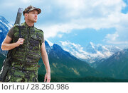 Купить «young soldier or hunter with gun over mountains», фото № 28260986, снято 14 августа 2014 г. (c) Syda Productions / Фотобанк Лори