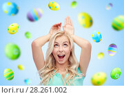 Купить «happy woman making bunny ears over easter eggs», фото № 28261002, снято 13 февраля 2016 г. (c) Syda Productions / Фотобанк Лори
