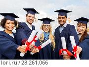 happy students in mortar boards with diplomas. Стоковое фото, фотограф Syda Productions / Фотобанк Лори