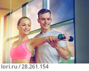 Купить «smiling young woman with personal trainer in gym», фото № 28261154, снято 29 июня 2014 г. (c) Syda Productions / Фотобанк Лори
