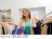 Купить «happy young woman choosing clothes in mall», фото № 28261350, снято 19 февраля 2016 г. (c) Syda Productions / Фотобанк Лори