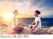 Купить «happy couple making yoga and meditating outdoors», фото № 28261450, снято 6 августа 2014 г. (c) Syda Productions / Фотобанк Лори