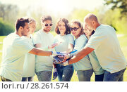 group of volunteers putting hands on top in park. Стоковое фото, фотограф Syda Productions / Фотобанк Лори
