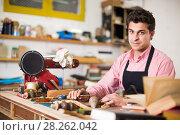 Купить «Craftsman in uniform working in carpentry», фото № 28262042, снято 8 апреля 2017 г. (c) Яков Филимонов / Фотобанк Лори