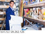 Sellerman in uniform is putting bags on the shelves in the building store. Стоковое фото, фотограф Яков Филимонов / Фотобанк Лори