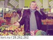 Купить «Glad man solving questions by phone in store», фото № 28262262, снято 13 февраля 2018 г. (c) Яков Филимонов / Фотобанк Лори