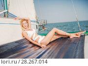 woman in fashion white swimsuit sitting on yacht. Стоковое фото, фотограф katalinks / Фотобанк Лори
