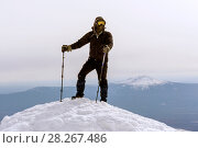 Mountaineer in a windproof mask and glasses reached the snow top of the mountain. Стоковое фото, фотограф Евгений Харитонов / Фотобанк Лори