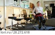 Купить «Portrait of happy girl sitting in comfortable office chair bought in furnishings store», видеоролик № 28272618, снято 28 марта 2018 г. (c) Яков Филимонов / Фотобанк Лори