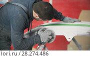 Купить «Man worker in uniform polishing car bumper in a service station», видеоролик № 28274486, снято 17 июля 2018 г. (c) Константин Шишкин / Фотобанк Лори