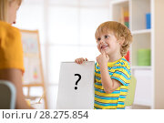 Young boy holding drawing during therapy or lesson with woman. Стоковое фото, фотограф Оксана Кузьмина / Фотобанк Лори