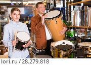 Купить «Father and teenage son examining drum units in guitar shop», фото № 28279818, снято 29 марта 2017 г. (c) Яков Филимонов / Фотобанк Лори