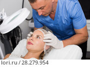 Купить «Doctor is examining woman patient before the procedure», фото № 28279954, снято 7 августа 2017 г. (c) Яков Филимонов / Фотобанк Лори