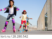 Купить «Happy girls learning forward slalom at skate park», фото № 28280542, снято 14 октября 2017 г. (c) Сергей Новиков / Фотобанк Лори