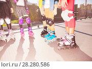 Купить «Kids rollerblading on road with protective gear», фото № 28280586, снято 14 октября 2017 г. (c) Сергей Новиков / Фотобанк Лори