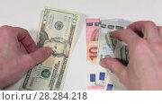 Купить «Пересчет денег в руках, купюры пять и десять евро и двадцатка в долларах, крупный план», видеоролик № 28284218, снято 26 февраля 2018 г. (c) Кекяляйнен Андрей / Фотобанк Лори