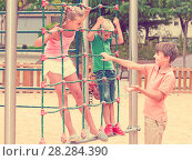 Купить «Kids are climbing on the grid on the playground.», фото № 28284390, снято 8 июля 2017 г. (c) Яков Филимонов / Фотобанк Лори
