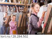 Купить «Schoolgirls with pleasure to draw a lesson», фото № 28284502, снято 21 мая 2018 г. (c) Яков Филимонов / Фотобанк Лори