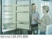 Купить «Husband and wife together choose for themselves refrigerator», фото № 28291806, снято 21 июля 2019 г. (c) Яков Филимонов / Фотобанк Лори