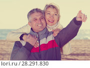 Купить «Mature couple walks outdoors and point by hand», фото № 28291830, снято 18 августа 2018 г. (c) Яков Филимонов / Фотобанк Лори